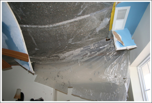 Plastic vapor barrier bulging under wet cellulose insulation.